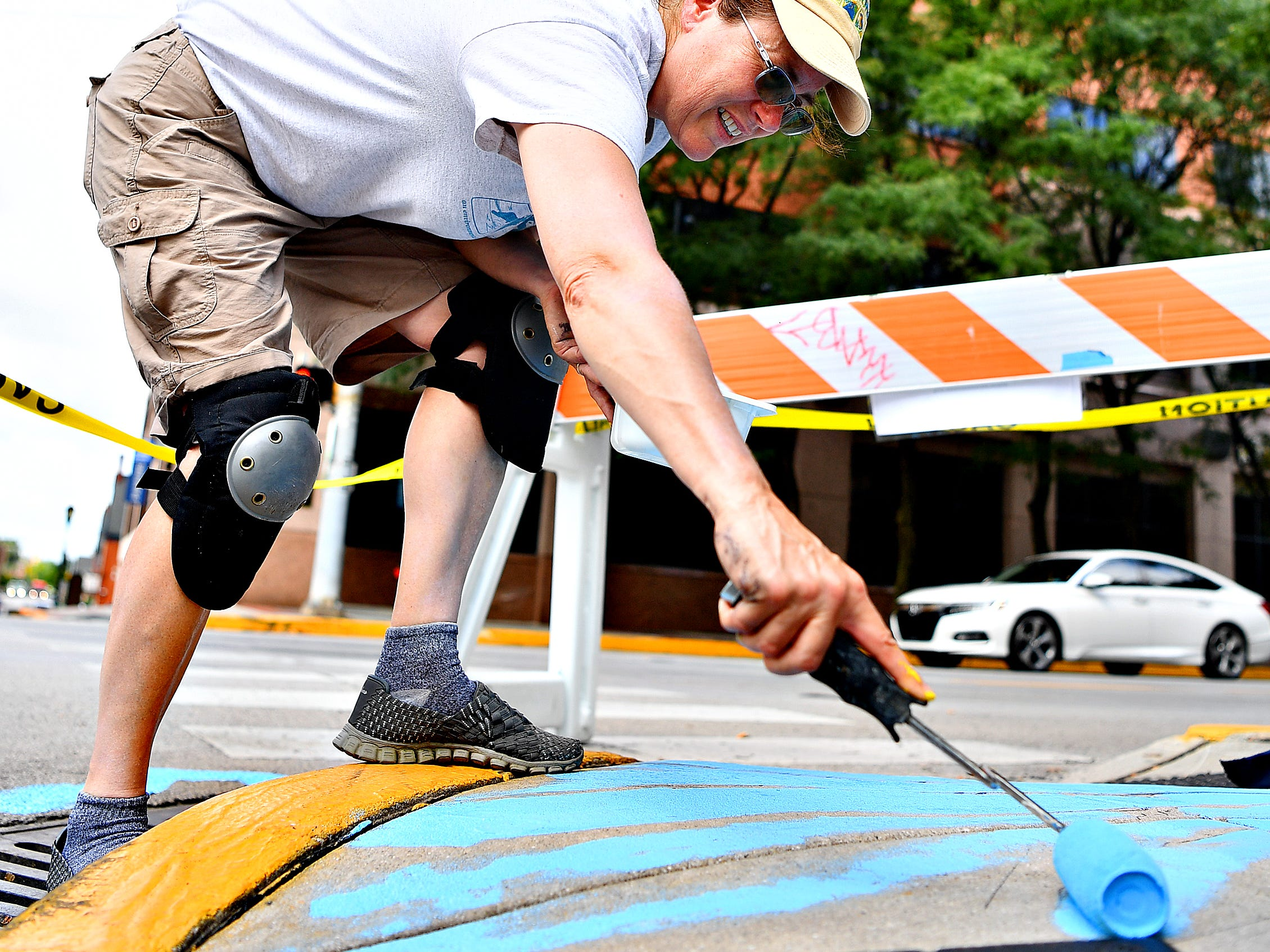 "Artist Linda Inners, of West Manchester Township, paints her storm drain art contest winning entry, ""Sea-cycle,"" at the corner of King and South George Streets in York City, Tuesday, Aug. 14, 2018. Inners' art is one of three pieces that will adorn storm drains in the city, with the others being placed where West Market Street meets the Heritage Rail Trail and the last in Continental Square near PeoplesBank, later in the week. Dawn J. Sagert"