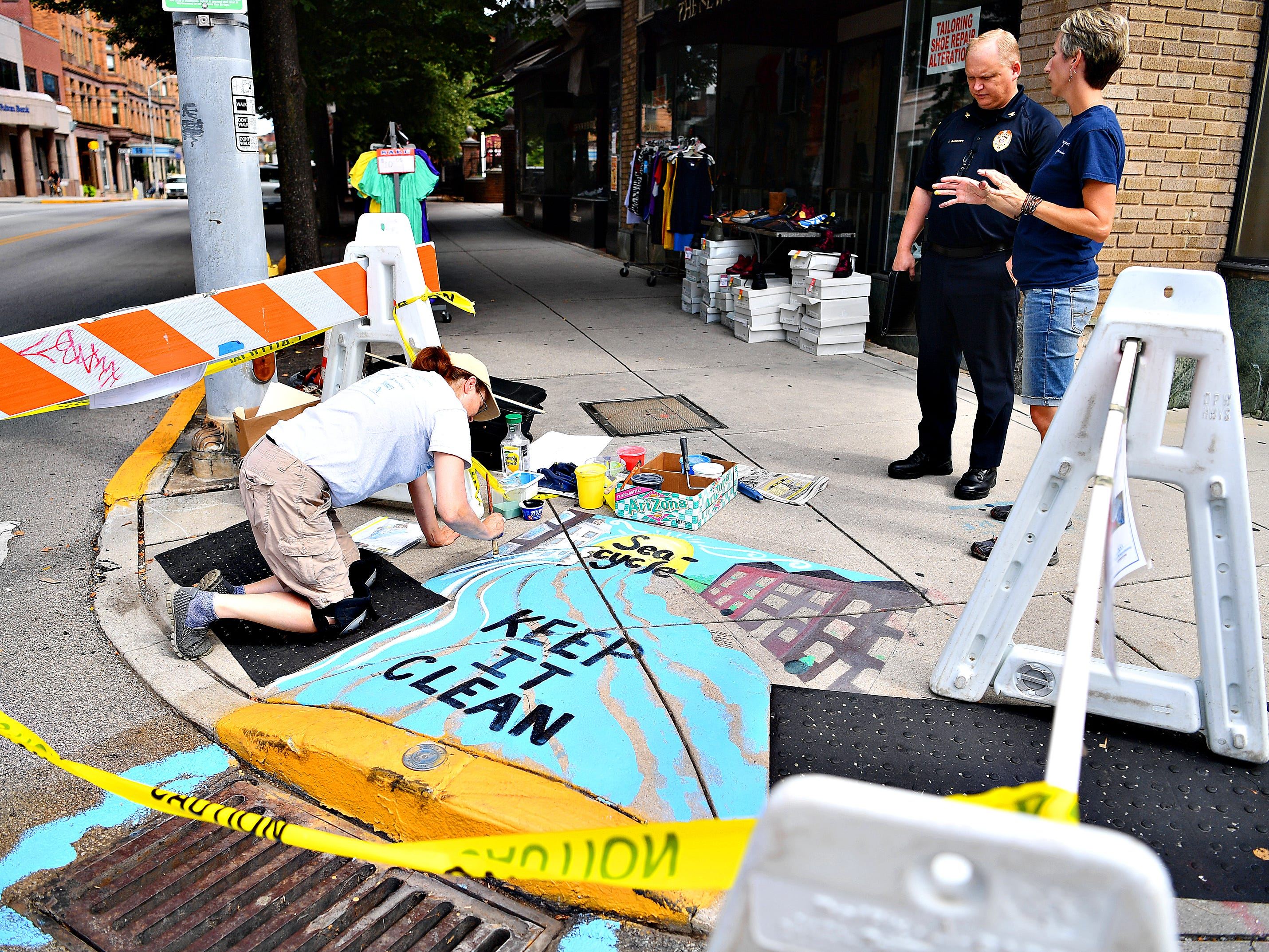 "Artist Linda Inners, left, of West Manchester Township, paints her storm drain art contest winning entry, ""Sea-cycle,"" at the corner of King and South George streets while Penn State York Extension master watershed steward coordinator Jodi Sulpizio, right, explains the project to York City Police Chief Troy Bankert in York City, Tuesday, Aug. 14, 2018. Inners' art is one of three pieces that will adorn storm drains in the city, with the others being placed where West Market Street meets the York County Heritage Rail Trail and in Continental Square near PeoplesBank later in the week. Dawn J. Sagert"