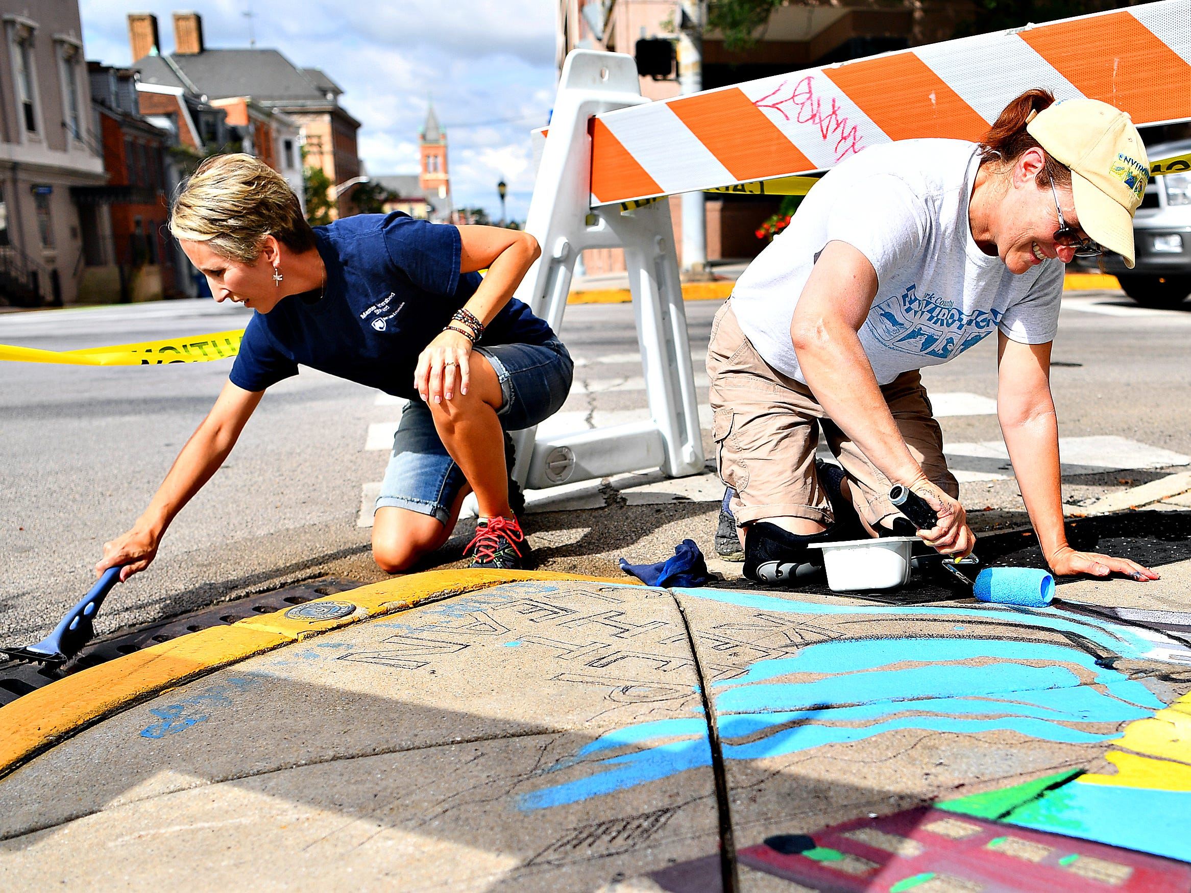 "Artist Linda Inners, right, of West Manchester Township, paints her storm drain art contest winning entry, ""Sea-cycle,"" at the corner of King and South George streets while Penn State York Extension master watershed steward coordinator Jodi Sulpizio sweeps the storm drain in York City, Tuesday, Aug. 14, 2018. Inners' art is one of three pieces that will adorn storm drains in the city, with the others being placed where West Market Street meets the York County Heritage Rail Trail and in Continental Square near PeoplesBank later in the week. Dawn J. Sagert"
