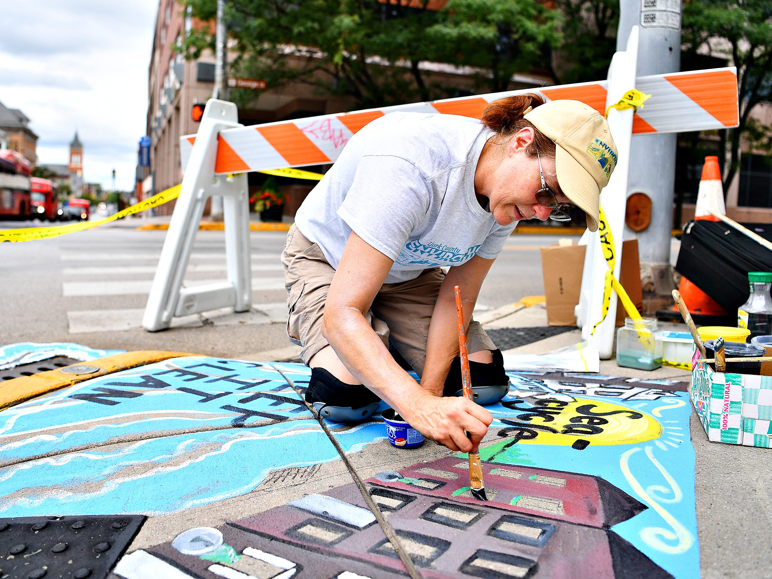 "Artist Linda Inners, of West Manchester Township, paints her storm drain art contest winning entry, ""Sea-cycle,"" at the corner of King and South George streets in York City, Tuesday, Aug. 14, 2018. Inners' art is one of three pieces that will adorn storm drains in the city, with the others being placed where West Market Street meets the York County Heritage Rail Trail and in Continental Square near PeoplesBank later in the week. Dawn J. Sagert"