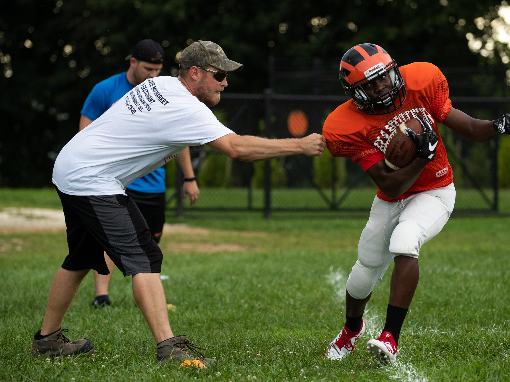 Coach Desch, one of the Hanover High School football team coaches, drills running backs on avoiding disruptions while running with the ball during practices on the first day of fall sports practice, Monday, Aug. 13, 2018, at the Sheppard-Meyers Stadium.