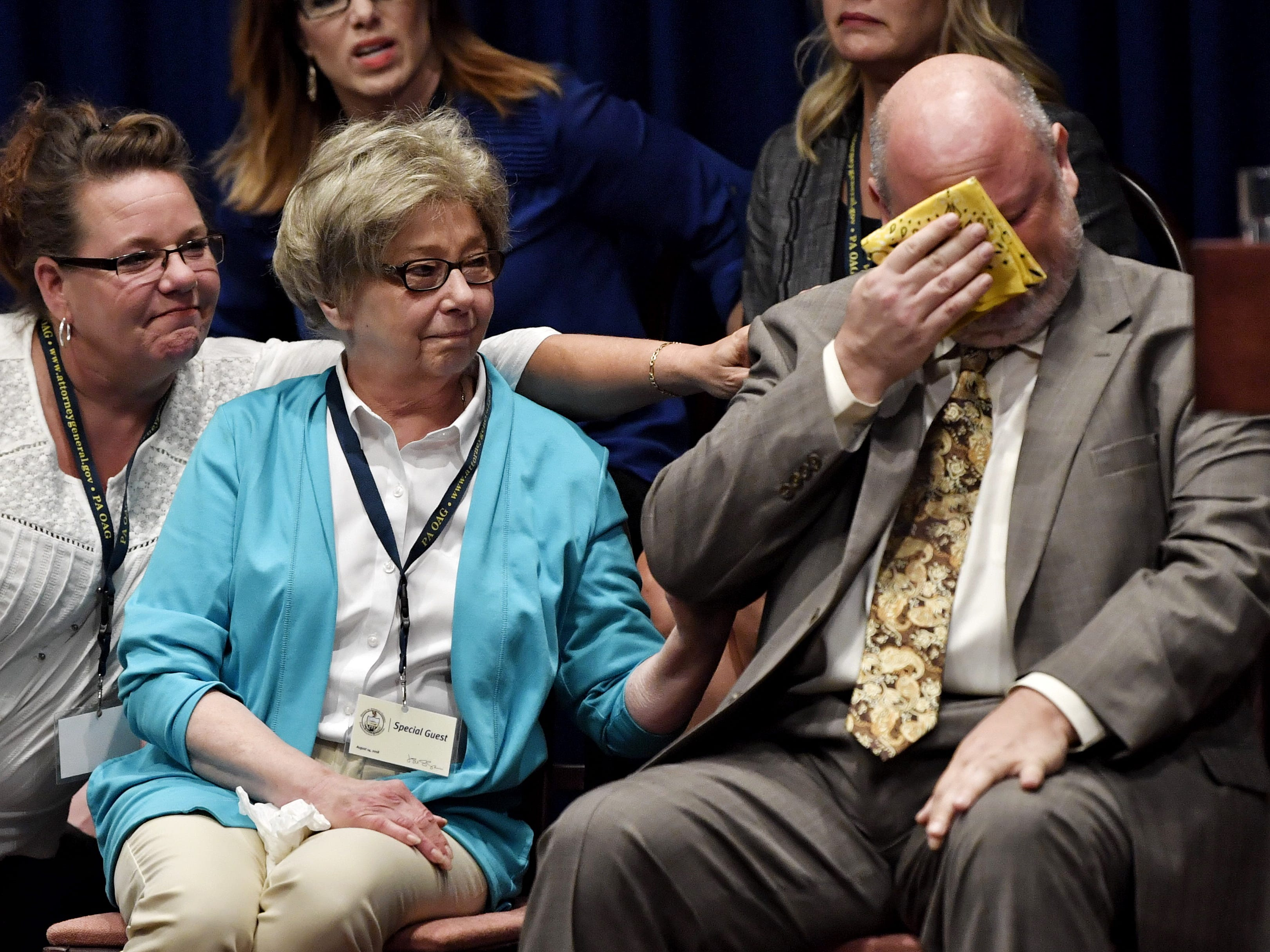 Survivors weep as Attorney General Josh Shapiro speaks during a new conference on the release of a grand jury report detailing decades of sexual abuse of children in six Catholic dioceses in Pennsylvania.