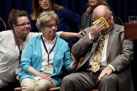 Juliann Bortz, center, helps comfort James Faluszczak, right, while Attorney General Josh Shapiro speaks during a news conference on the release of a grand jury report detailing decades of sexual abuse of children in six Catholic dioceses in Pennsylvania.