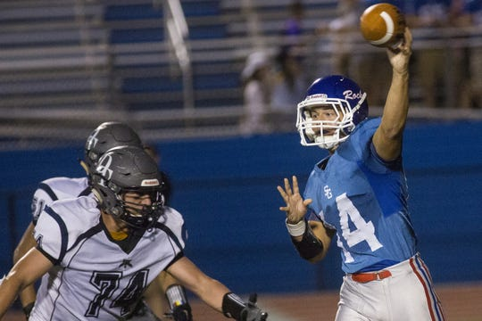 Dallastown's Raymond Christas, left, pursues Spring Grove quarterback Nick Shaqfeh. Dallastown defeats Spring Grove 23-14 in football at Papermakers Stadium in Spring Grove, Friday, September 23, 2016.