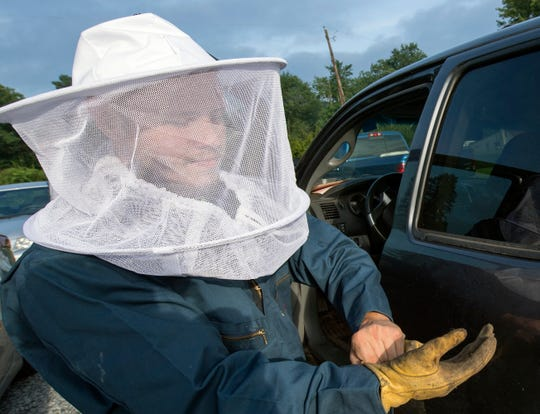 Mike Ellis, 23, works a wildlife control business all over York County with his father. Here, the son suits up in a beekeepers' suit to insert silicate dust into a hornets' nest.