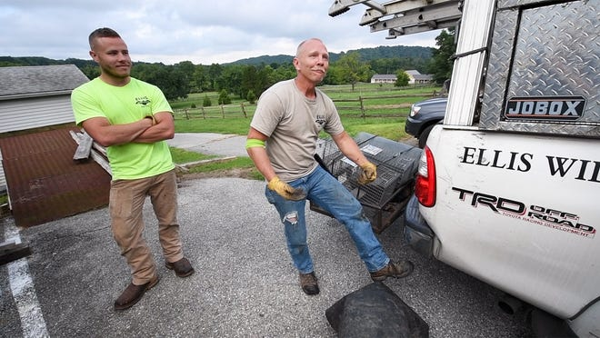 Mike Ellis, right, describes an alligator coming under the seat of his Toyota Corolla while he was transporting it, three cats and a dog to the SPCA. His son Mike listens at left. The pair were picking up raccoons that were getting into a barn and eating animal feed.