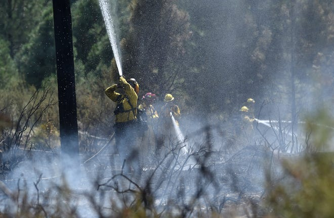 Firefighters work to put out a wildfire that broke out next to the Gold Ranch R.V. Resort in Verdi on Aug. 14, 2018.