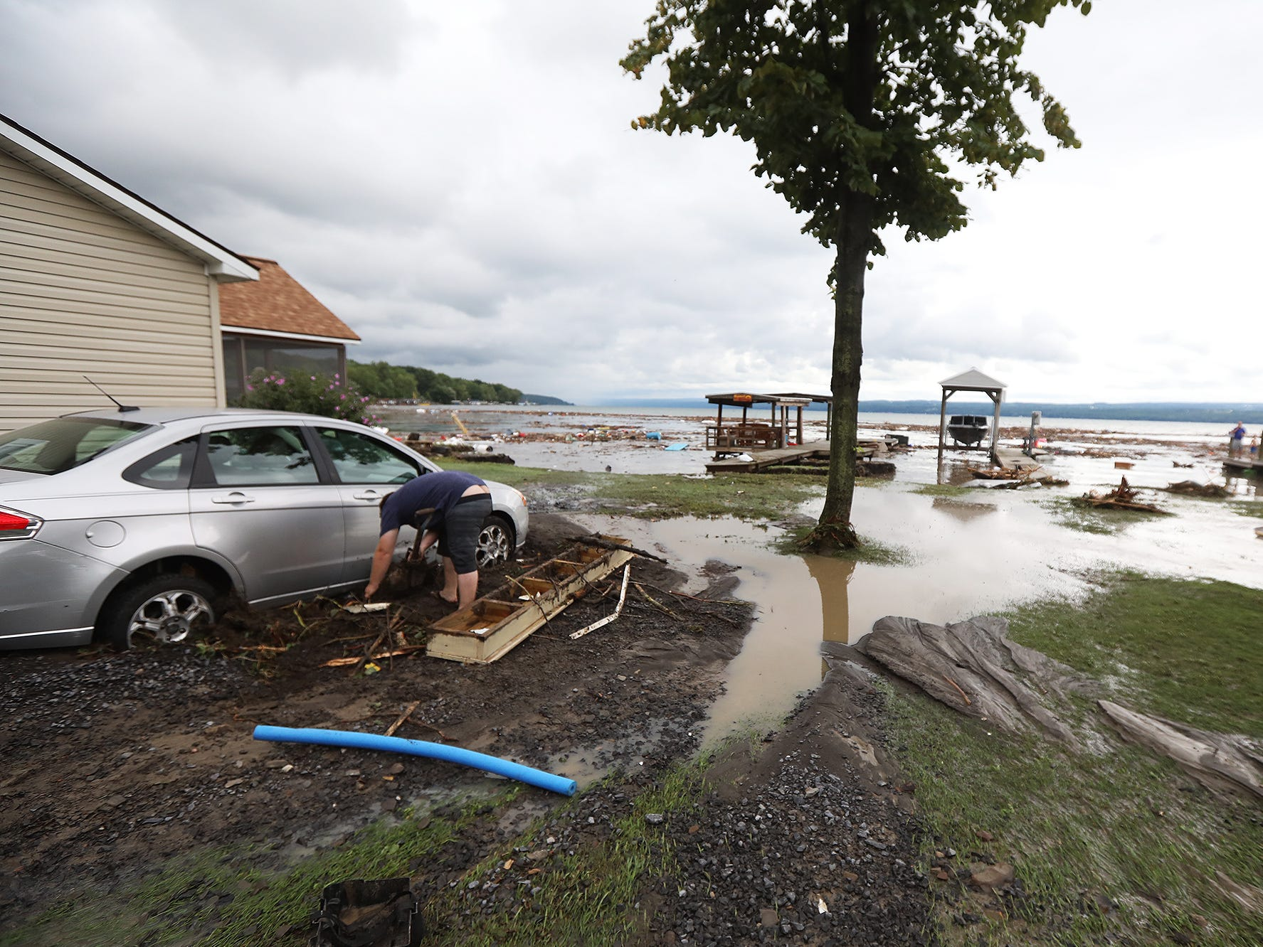 Andrew Skinner of Virginia tries to dig out his car that is stuck in a few feet of mud after heavy rain caused flooding and washing away at Lodi Point, New York on Tuesday, August 14, 2018.