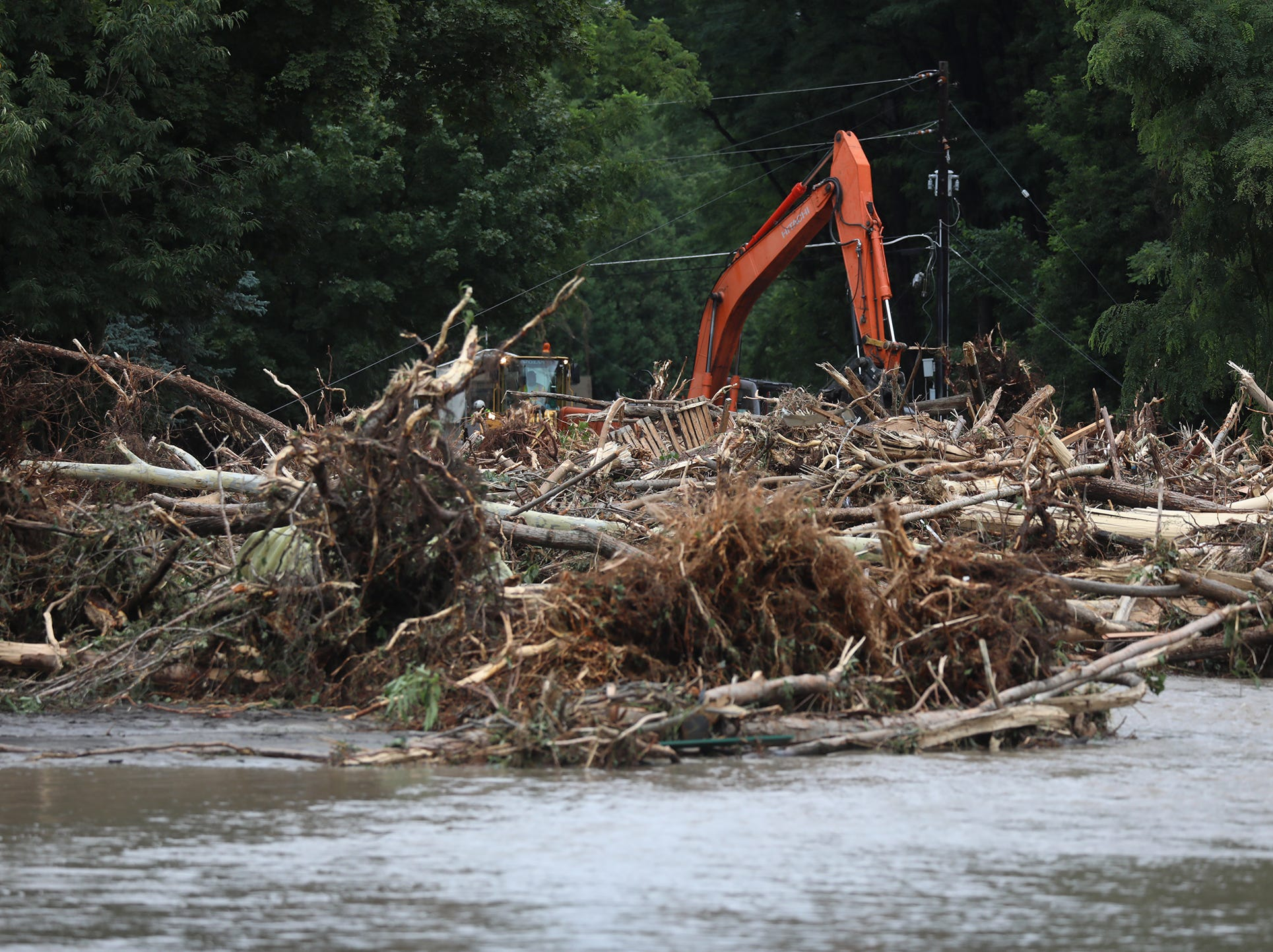 A huge pile of trees obscure a portion of Lower Lake Road after heavy rain caused flooding and washing away at Lodi Point, New York on Tuesday, August 14, 2018.