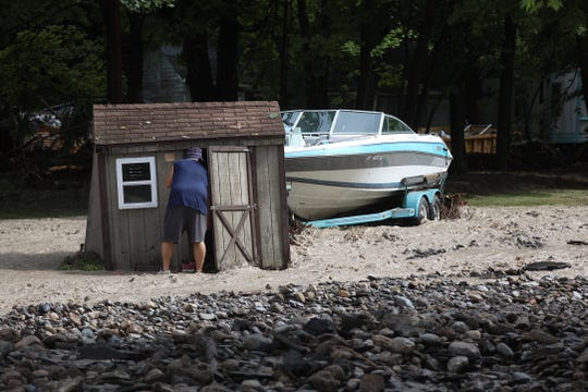 A resident checks a shed surrounded by water after heavy rain caused flooding and washing away at Lodi Point.  His home was at the bottom of a hill and still had water flowing rapidly all around it heading into nearby Seneca Lake.