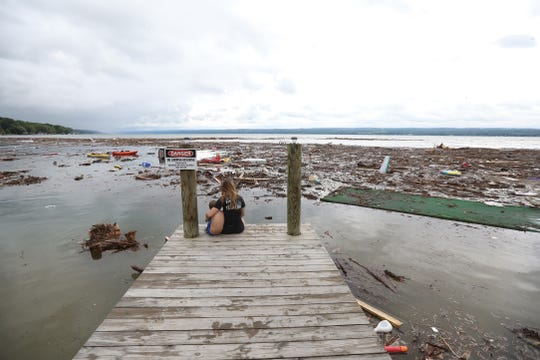 Hannah Shelby sits with her step sibling Aiden Patterson at the end of the dock on Seneca Lake after heavy rain caused flooding and washing away at Lodi Point.   They were on vacation with their parents when flooding woke them up.  The family lives in LeRoy, NY.