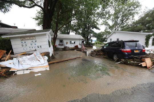 A shed is knocked off its foundation and a minivan is surrounded with debris after heavy rain caused flooding and washing away at Lodi Point, New York on Tuesday, August 14, 2018.
