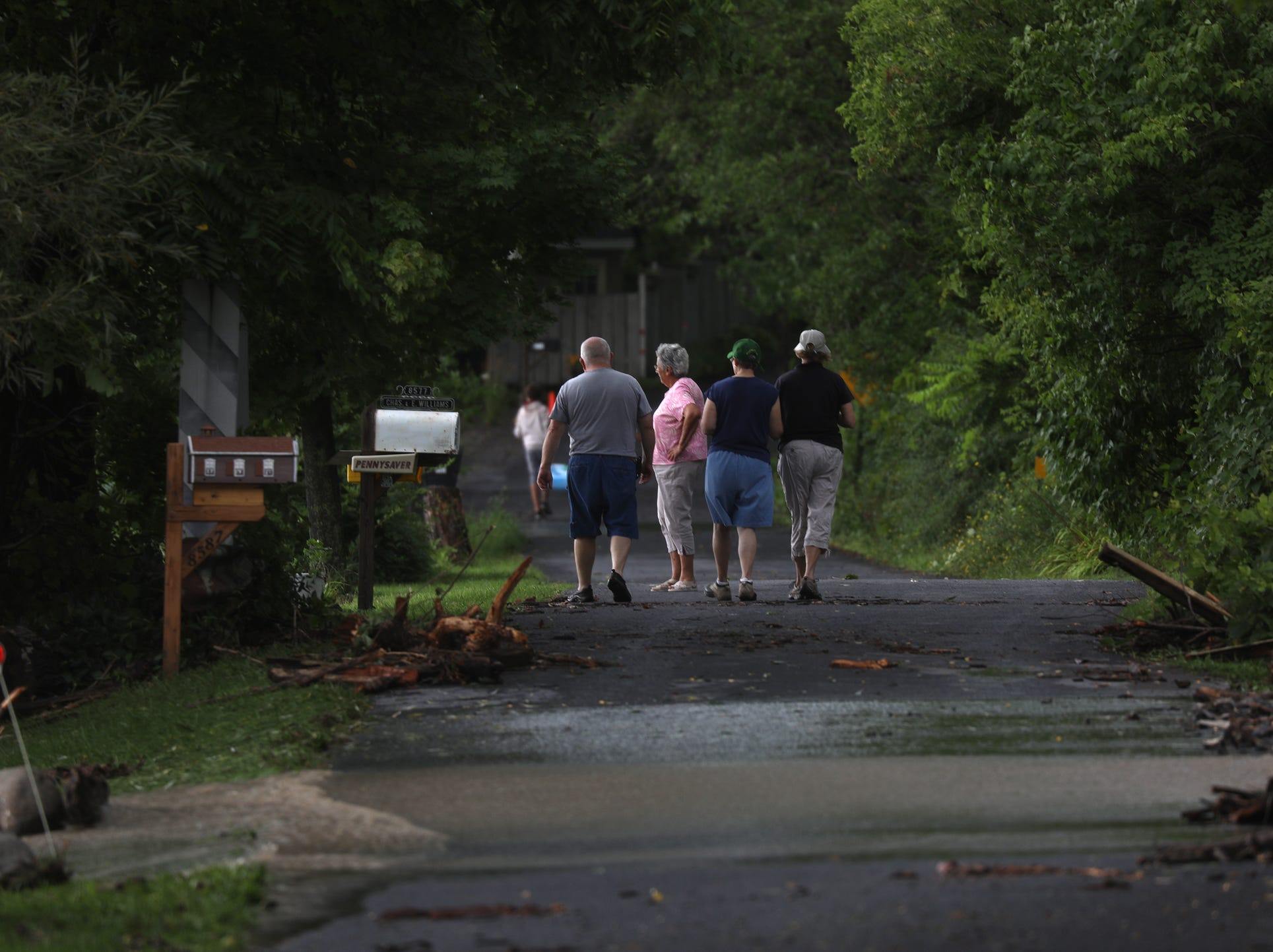 Many residents and vacationers stopped and talked and assessed damage after heavy rain caused flooding and washing away at Lodi Point, New York on Tuesday, August 14, 2018.