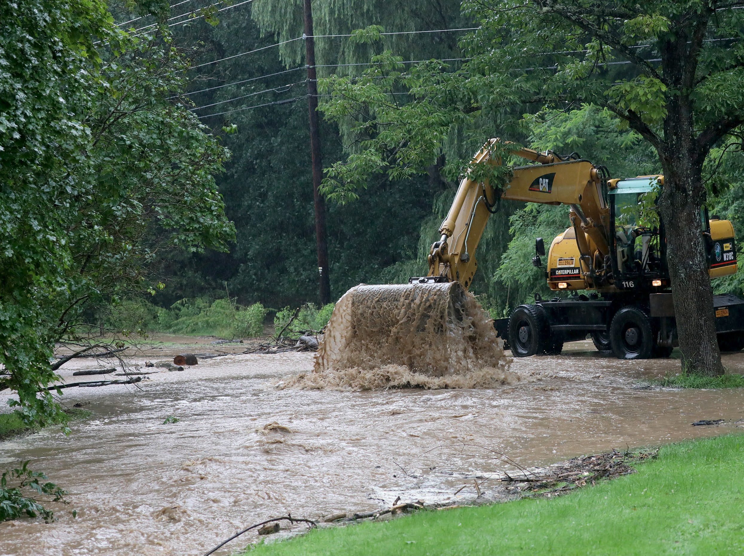 Crews work to unclog storm drains that clogged and flooded Park Rd. In Powder Mills Park near the fish hatchery.