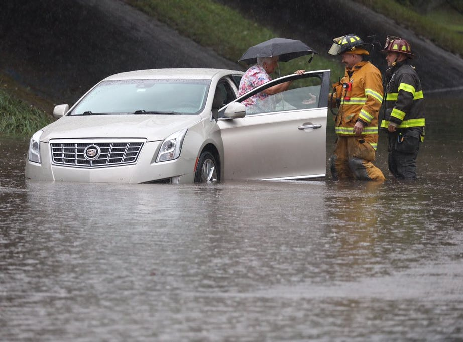 Tim Young and Sal Tantlo with the Bushnell's Basin Fire Department help a woman stuck in flooding on Garnsey Road.
