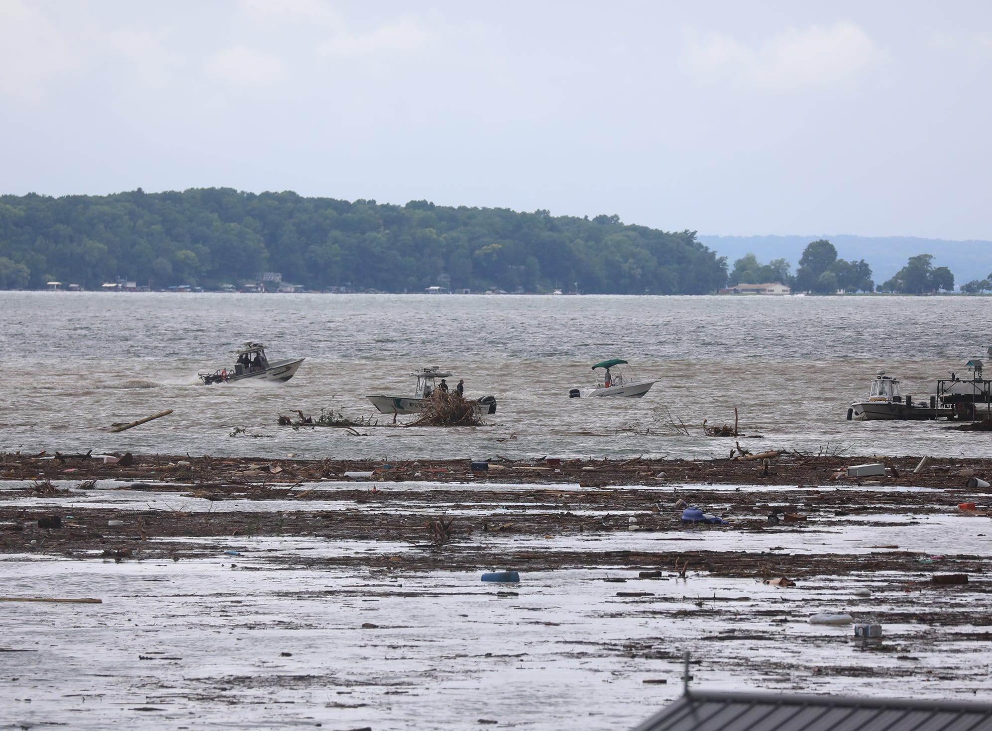 Several boats head to Lodi Point to evacuate people after heavy rain caused flooding and washing away at Lodi Point, New York on Tuesday, August 14, 2018.