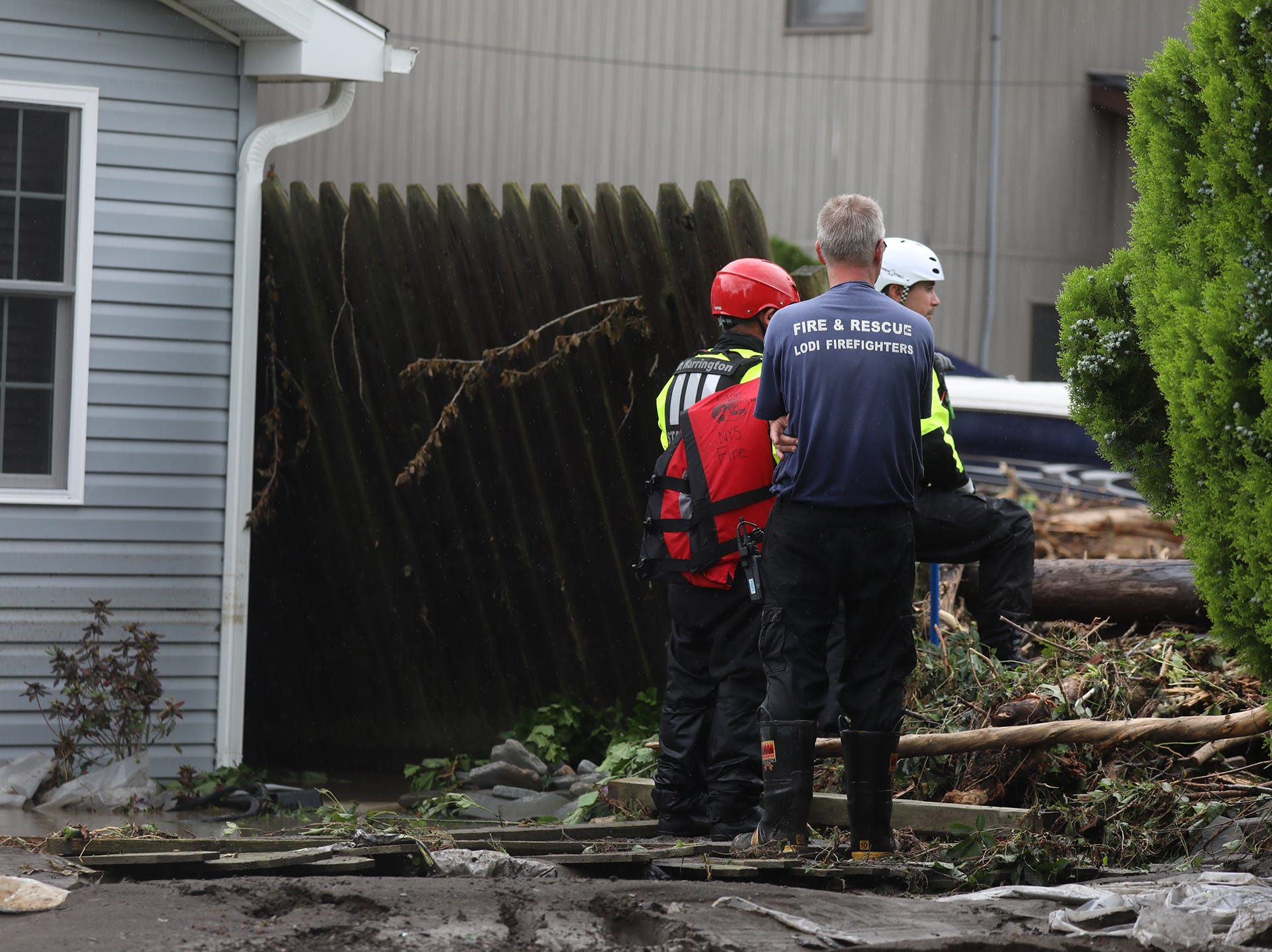 Lodi water rescue personnel go door to door in the heaviest effect area after heavy rain caused flooding and washing away at Lodi Point, New York on Tuesday, August 14, 2018.