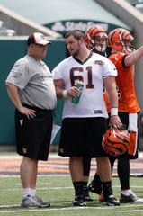 Cincinnati Bengals fourth round draft pick Russell Bodine, a center from North Carolina, (61) talks with offensive line coach Paul Alexander during an NFL football mandatory minicamp, Tuesday, June 10, 2014, in Cincinnati. Alexander is a Rochester native and Bodine is now a free agent center with the Buffalo Bills.