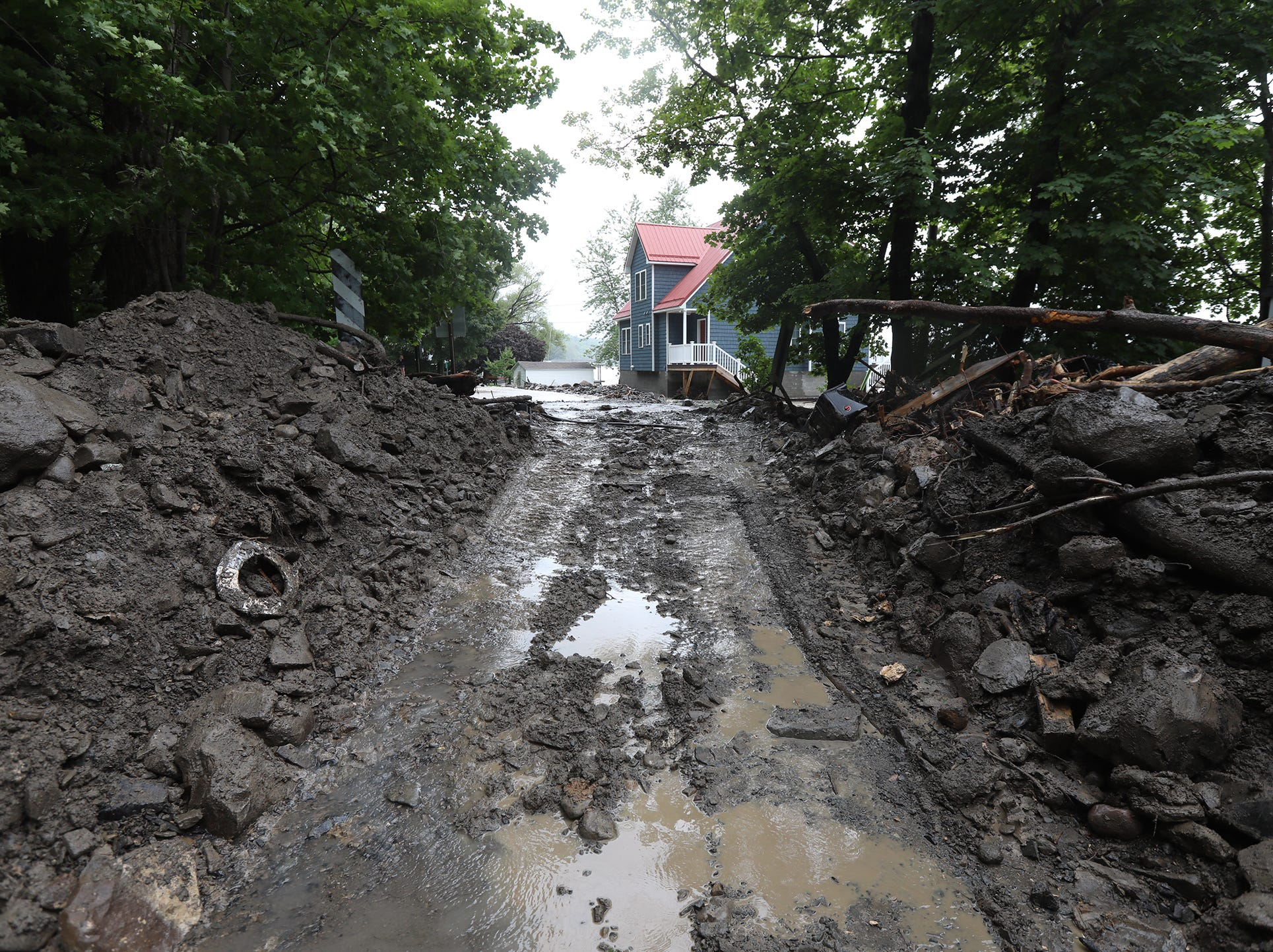 Workers were able to clear a passable area of Lower Lake Road after heavy rain caused flooding and washing away at Lodi Point, New York on Tuesday, August 14, 2018.