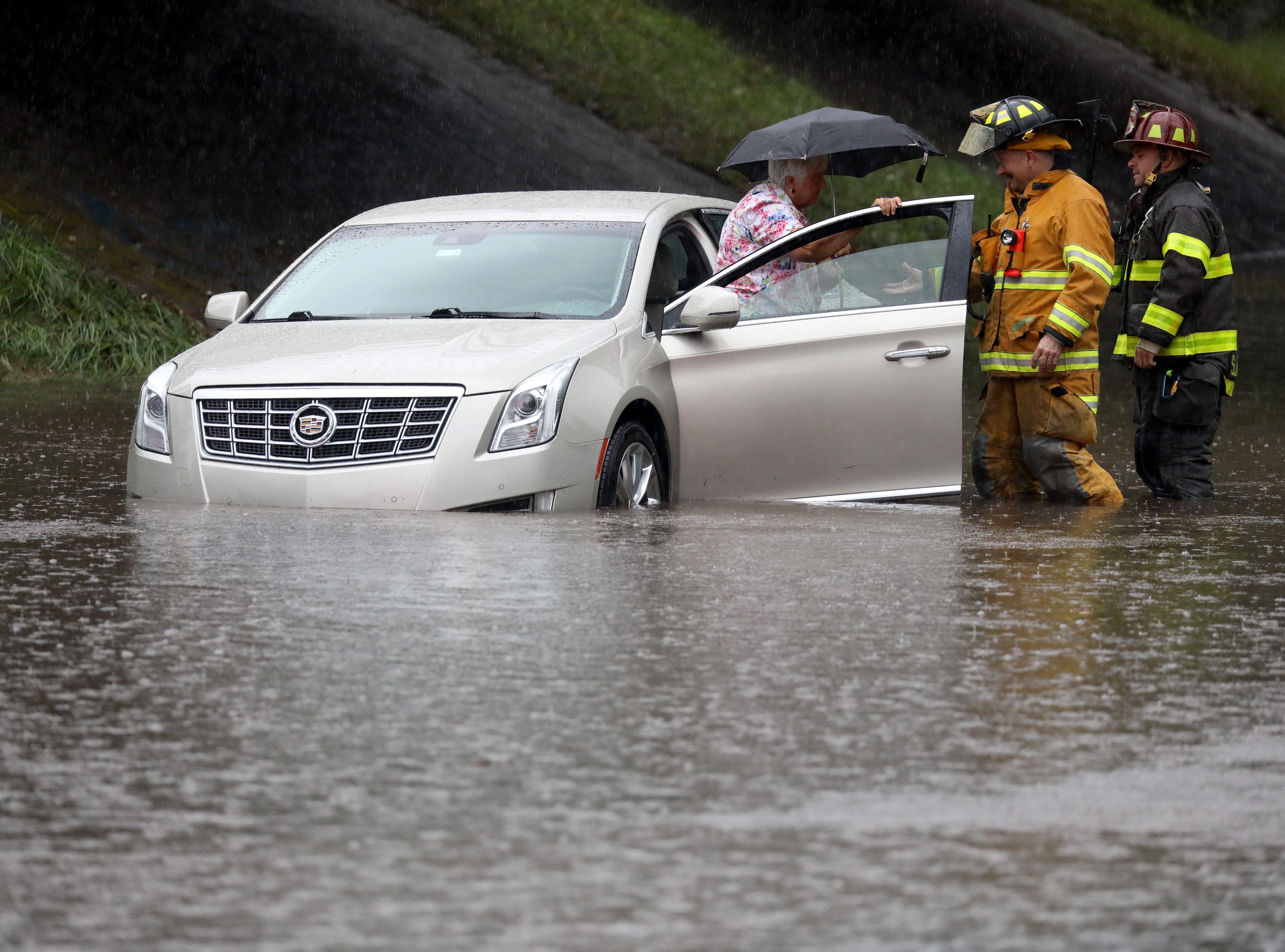 Tim Young and Sal Tantlo with Bushnell's Basin Fire Department, help a woman from her car after it became trapped in flooding on Garnsey Rd.