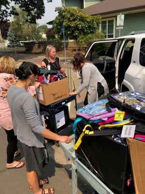 Volunteers from Salem Health Medical Clinics deliver backpacks Tuesday, Aug. 14, 2018, to Bush Elementary School.