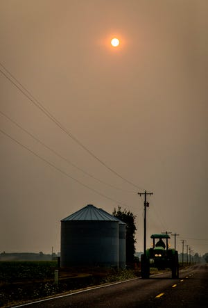 A tractor heads west on Waconda Road NE near Brooks early Tuesday morning, August 14, 2018,  as the sun peeks through a thick layer of wildfire smoke that has blanketed the Willamette Valley.