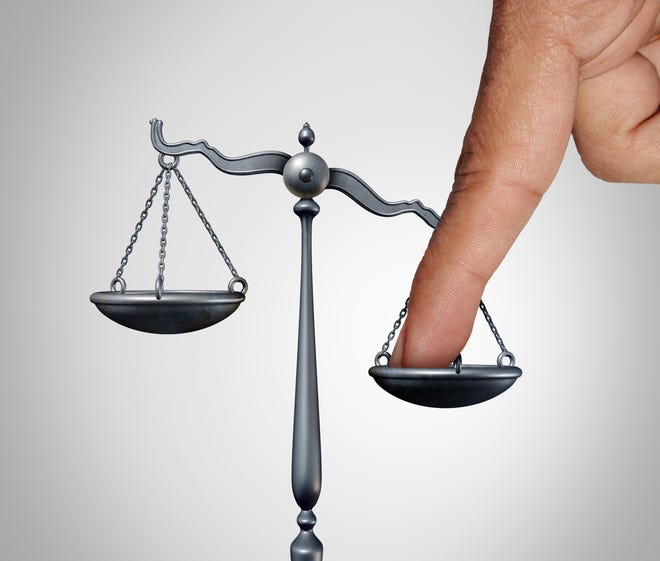 Tipping the scales of justice illustration.