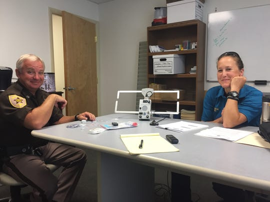 Sgt. Chad Kellam and Investigator Tara Leckel of the Northampton County Sheriff's Office display a receiver and other items associated with Project Lifesaver, on Monday, Aug. 13, 2018 in Eastville, Virginia.