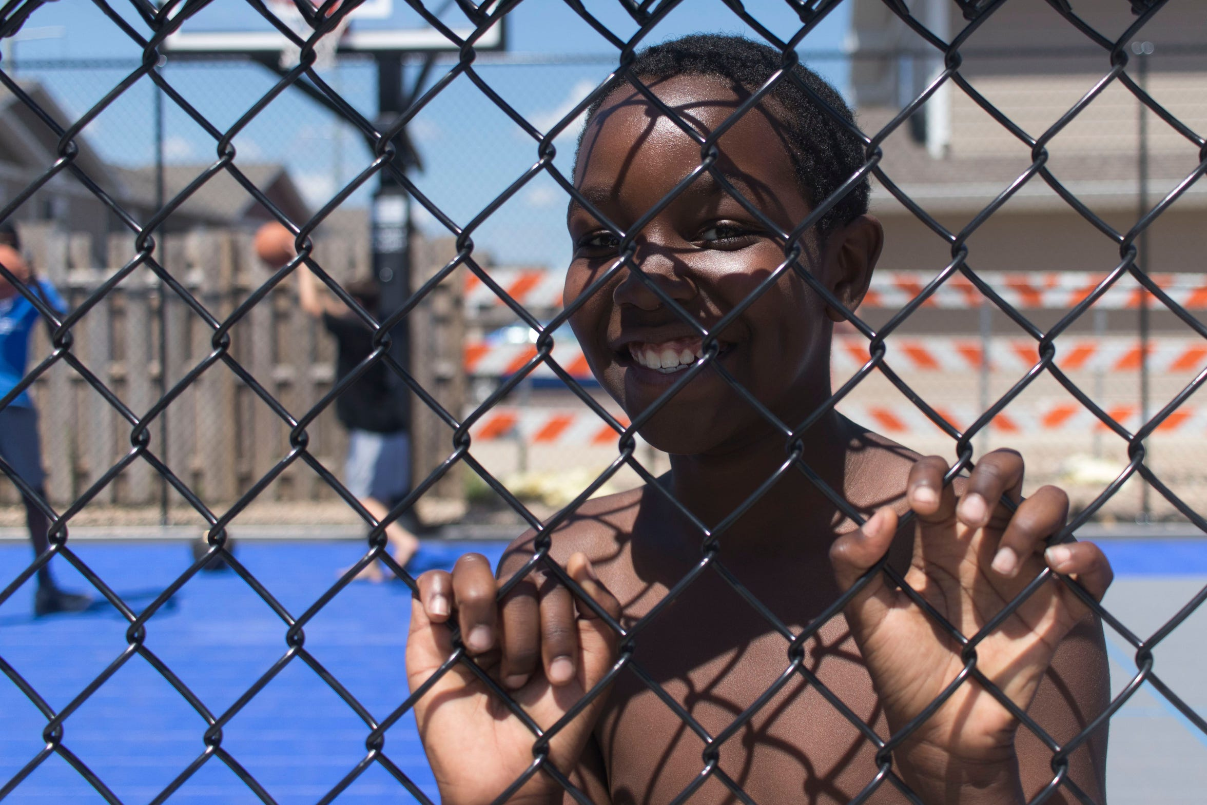 "A child at the after-school ""pop-up"" program smiles through the chain link fence. The middle school-aged children often play basketball together with facilitators behind their apartment as part of the program."