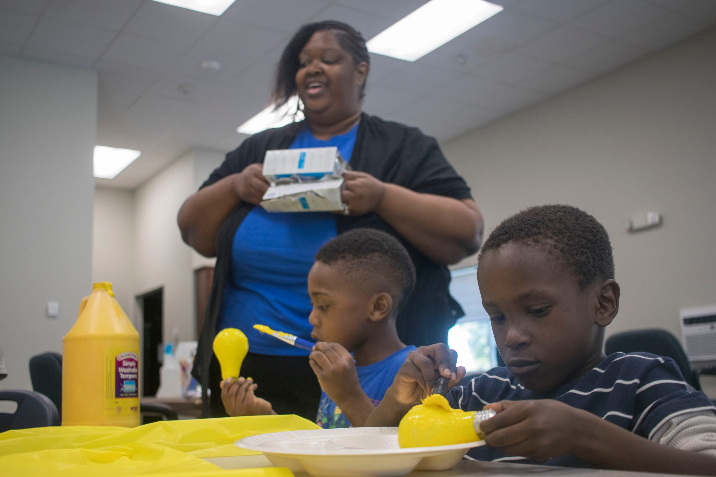 "Cynthia Robinson, a Boys and Girls Club facilitator, teaches two children how to turn lightbulbs into bees at a new ""pop-up"" club at Horizon Place Apartments. The program caters to unsupervised children where they're at by bringing after-school or out-of-school time activities directly to the public housing complex."