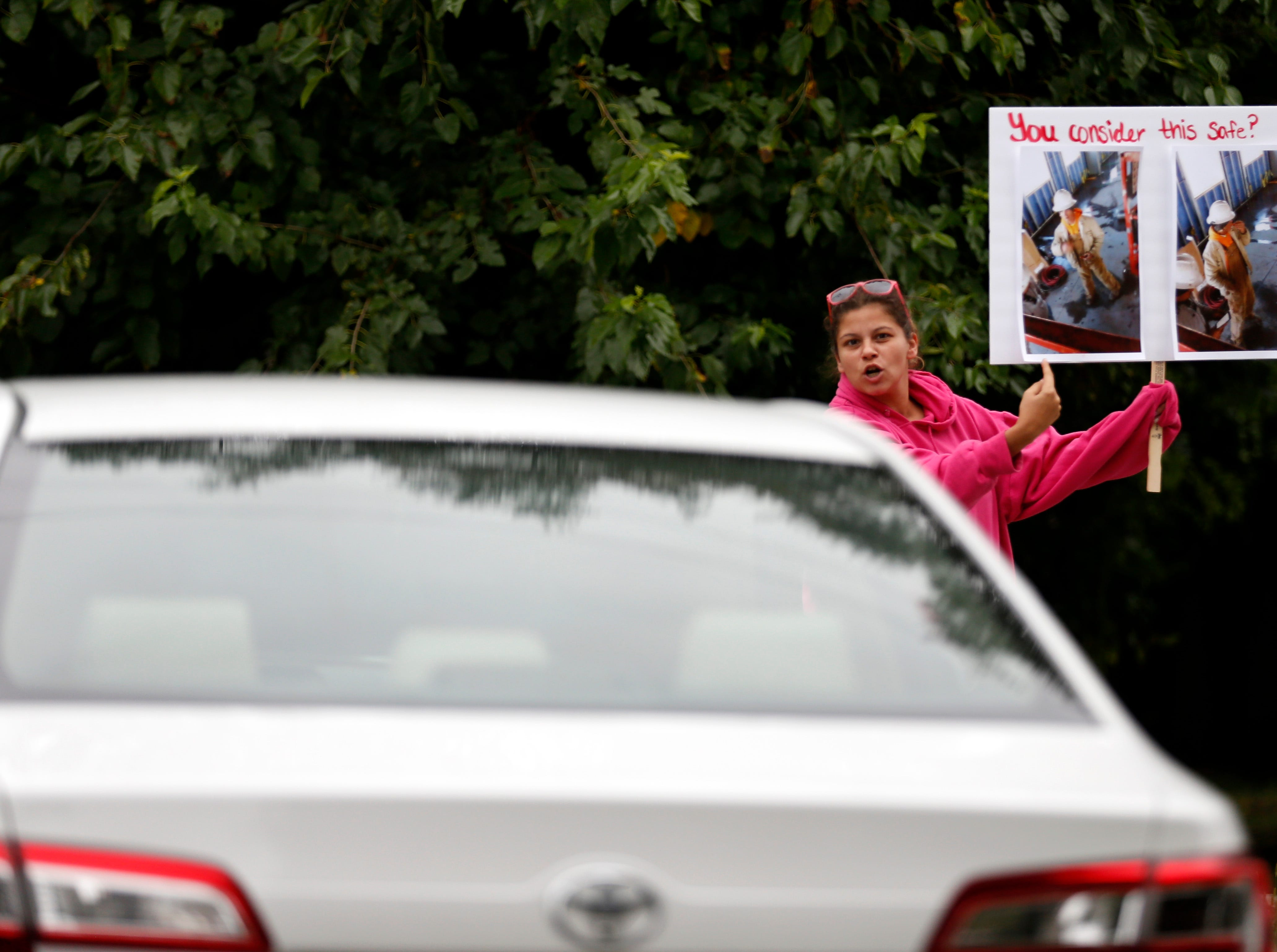 A counter-protestor points at her sign as protestors leave in cars along West Farm Road 146 outside DelCo Construction on Tuesday, Aug. 14, 2018. Protestors claimed that DelCo and its owner, Jeff Delmont, subject workers to unsafe conditions, low wages, and inadequate training while counter-protestors pushed back against the allegations.