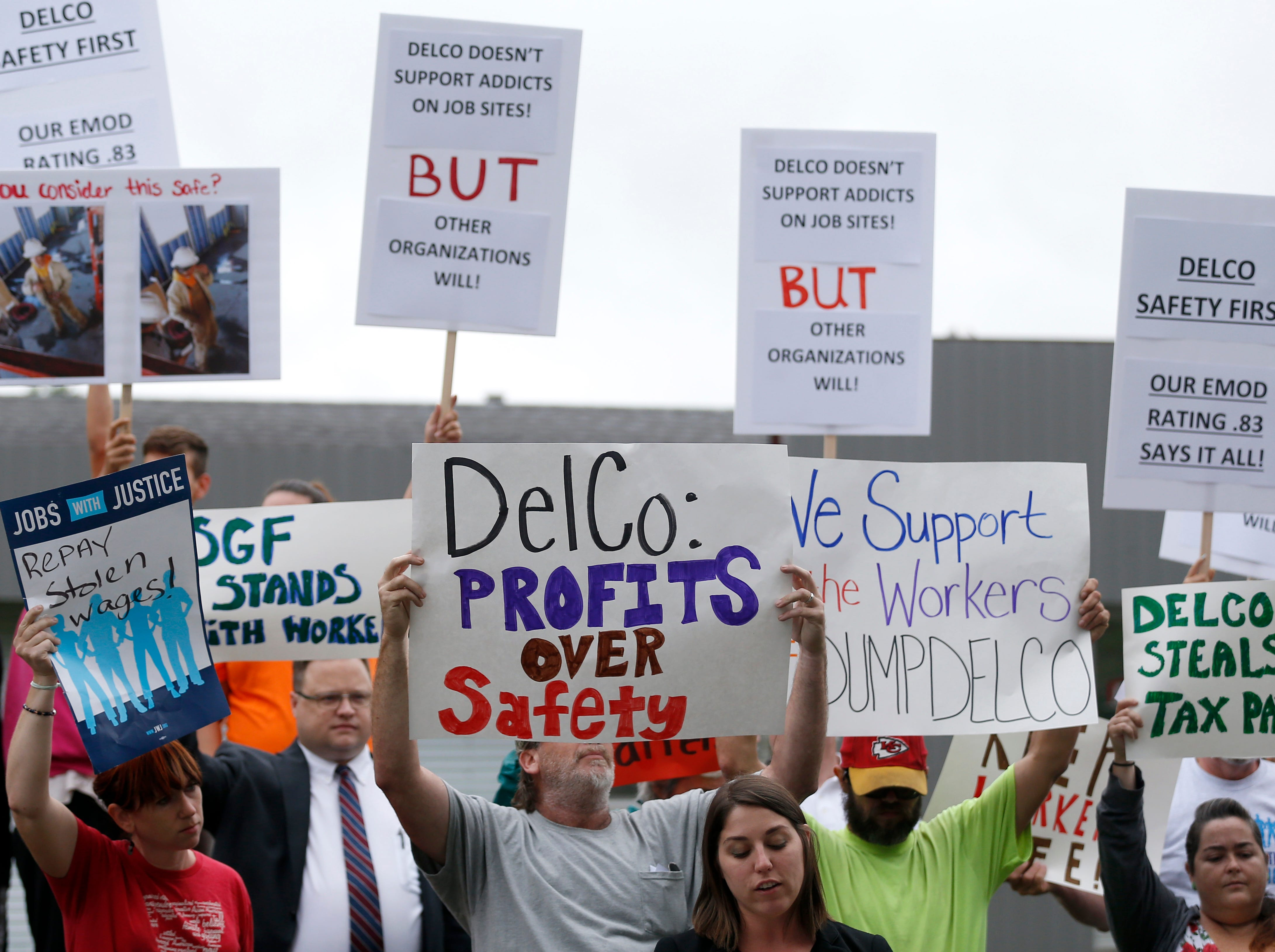 Rep. Crystal Quade, D-Springfield speaks to a group of protestors outside DelCo Construction on Tuesday, Aug. 14, 2018 while counter-protestors stand behind them. Protestors claimed that DelCo and its owner, Jeff Delmont, subject workers to unsafe conditions, low wages, and inadequate training.