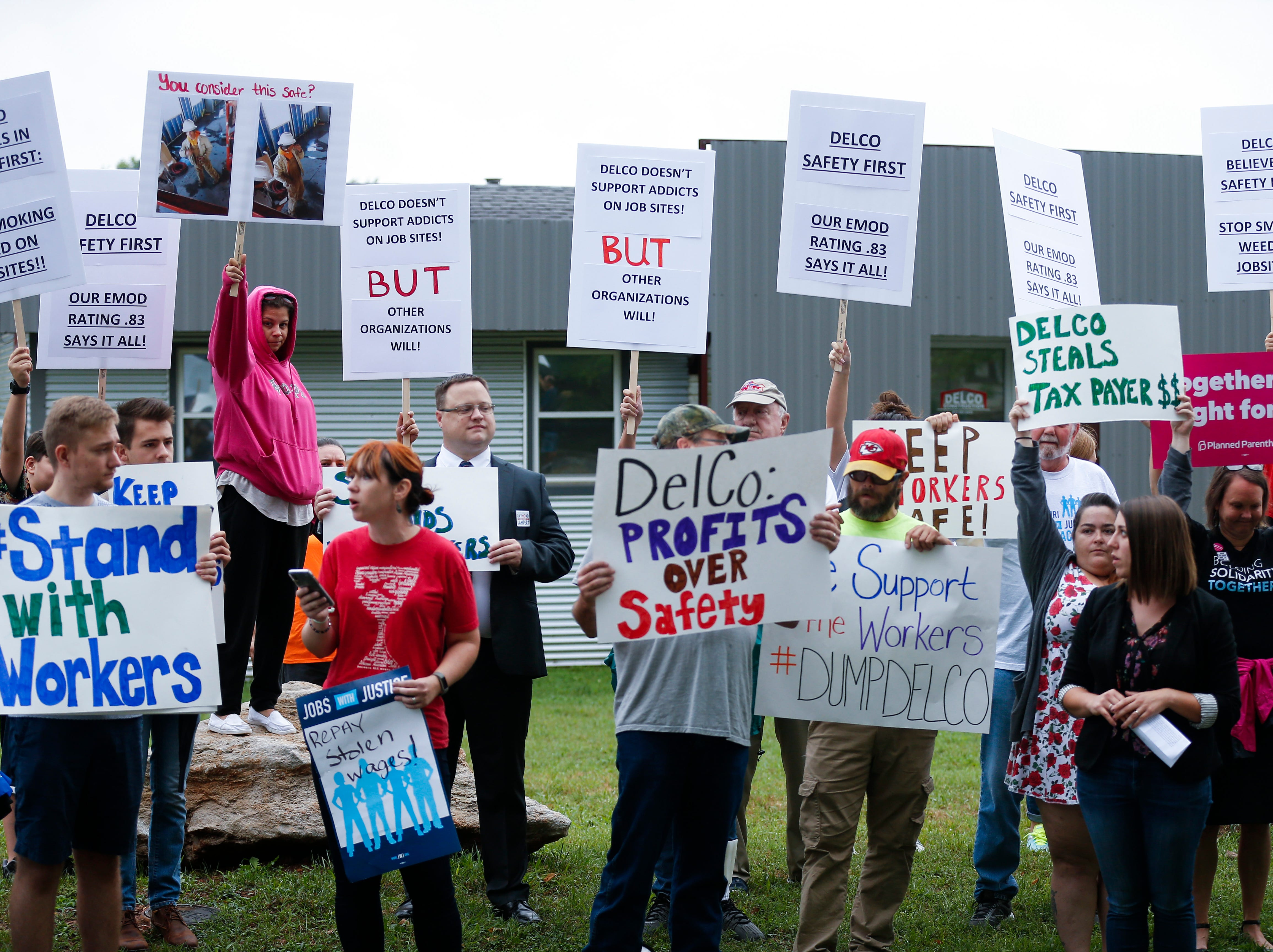 Protestors and counter-protesters behind them, stand along West Farm Road 146 outside DelCo Construction on Tuesday, Aug. 14, 2018. Protestors claimed that DelCo and its owner, Jeff Delmont, subject workers to unsafe conditions, low wages, and inadequate training while counter-protestors pushed back against the allegations.