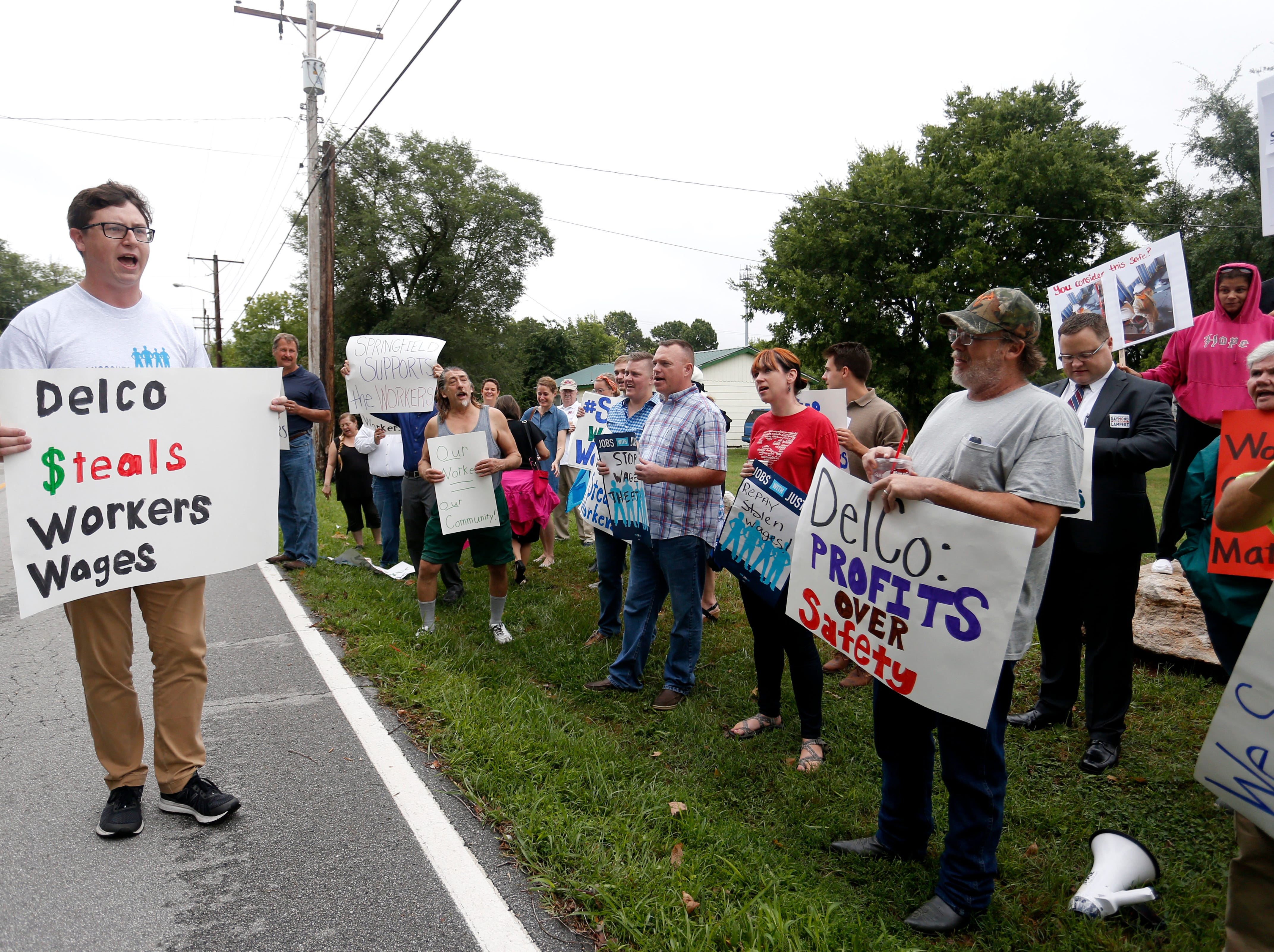 Alex Johnson leads a chant outside DelCo Construction on Tuesday, Aug. 14, 2018. Protestors claimed that DelCo and its owner, Jeff Delmont, subject workers to unsafe conditions, low wages, and inadequate training.