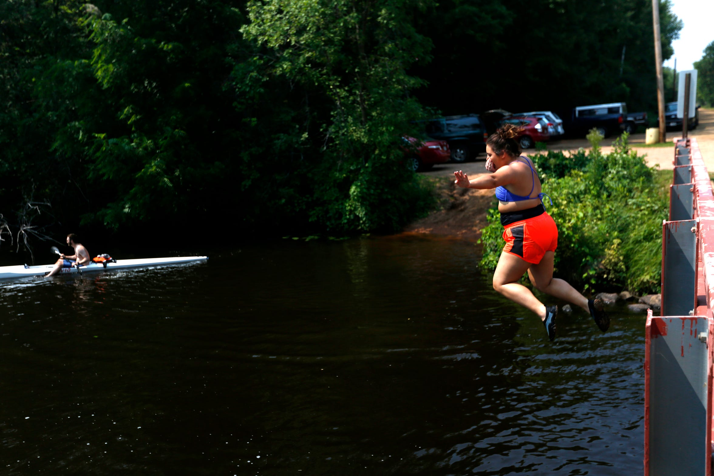 A quester jumps into the river to complete a challenge during PaddleQuest Odyssey in Stevens Point, Wis., August 11, 2018.