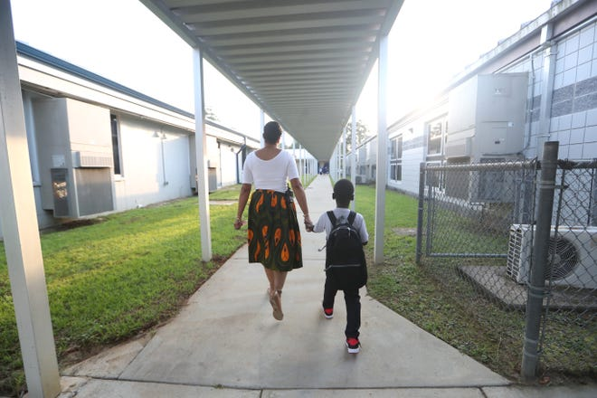 Principal Carmen Conner helps Peter Erhiawarie, 5, find his classroom on the first day of school at Pineview Elementary on Monday.