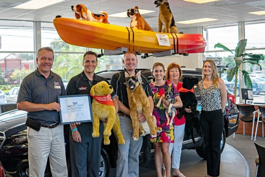 Dyer Subaru Manager Chad Bierle, left, Dyer Vero Beach Manager Jonathan Hardie, Will and Tatiana Dyer -- holding Trooper, who is available for adoption -- present the August Dyer Difference Dyer Charity Month Award to H.A.L.O.'s No-Kill Rescue Jan Howington and Ashley Novander.