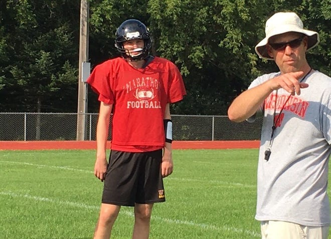First-year Marathon football coach Ryan Winkler, right, gives instructions to his players during a recent practice as quarterback/defensive back Clarke Mouw looks on.