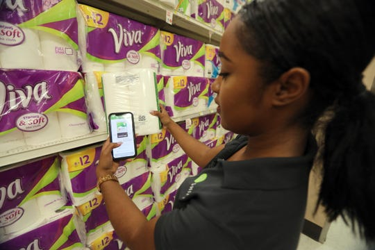 Destinee Rayford, City Launch manager for SHIPT, an app that allows shoppers to order online and have the order delivered to their home, uses the app to scan the barcode on a package of paper towels for an order during a demonstration of the app at the Target in White Plains Aug. 14, 2018.