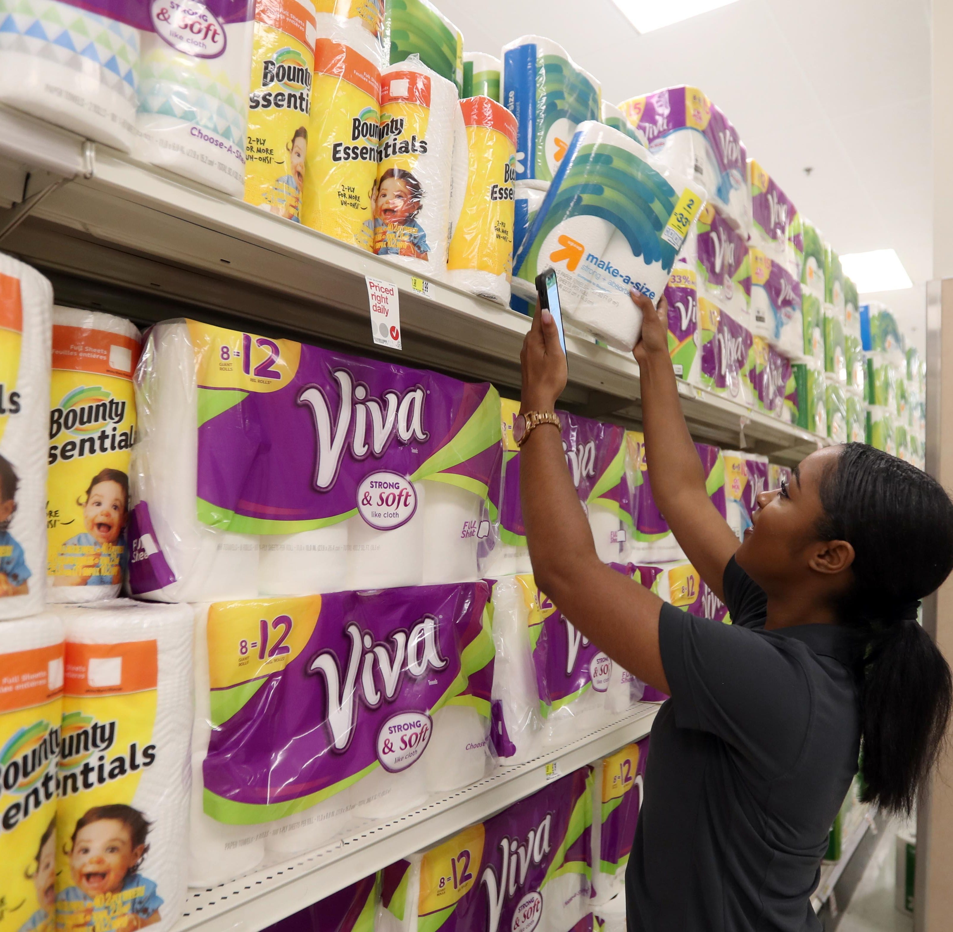 Destinee Rayford, City Launch manager for SHIPT, an app that allows shoppers to order online and have the order delivered to their home, uses the app to find the correct brand of paper towels for an order during a demonstration of the app at the Target in White Plains Aug. 14, 2018.