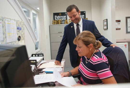 Tim Carter, sale manager at Patterson-Schwartz Real Estate's Brandywine office helps office administration assistant Kelley Quinn with an issues. Patterson-Schwartz Real Estate was named 1st in Large Company for Delaware Top Workplaces.