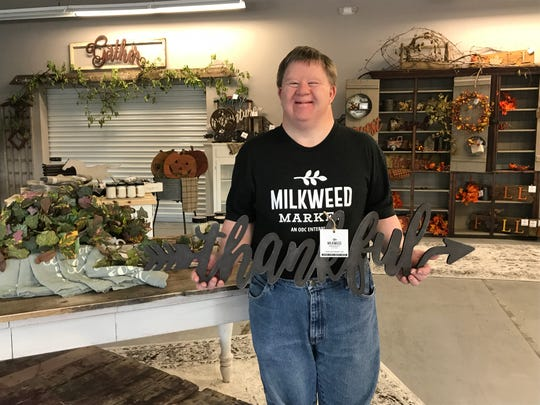 "Mark Peters holds a ""thankful"" sign in Milkweed Market's new retail store at ODC in Wisconsin Rapids."