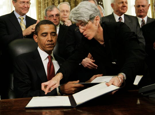 White House staff secretary Lisa Brown helps President Barack Obama as he signs a series of executive orders on the third day of his presidency in 2009.