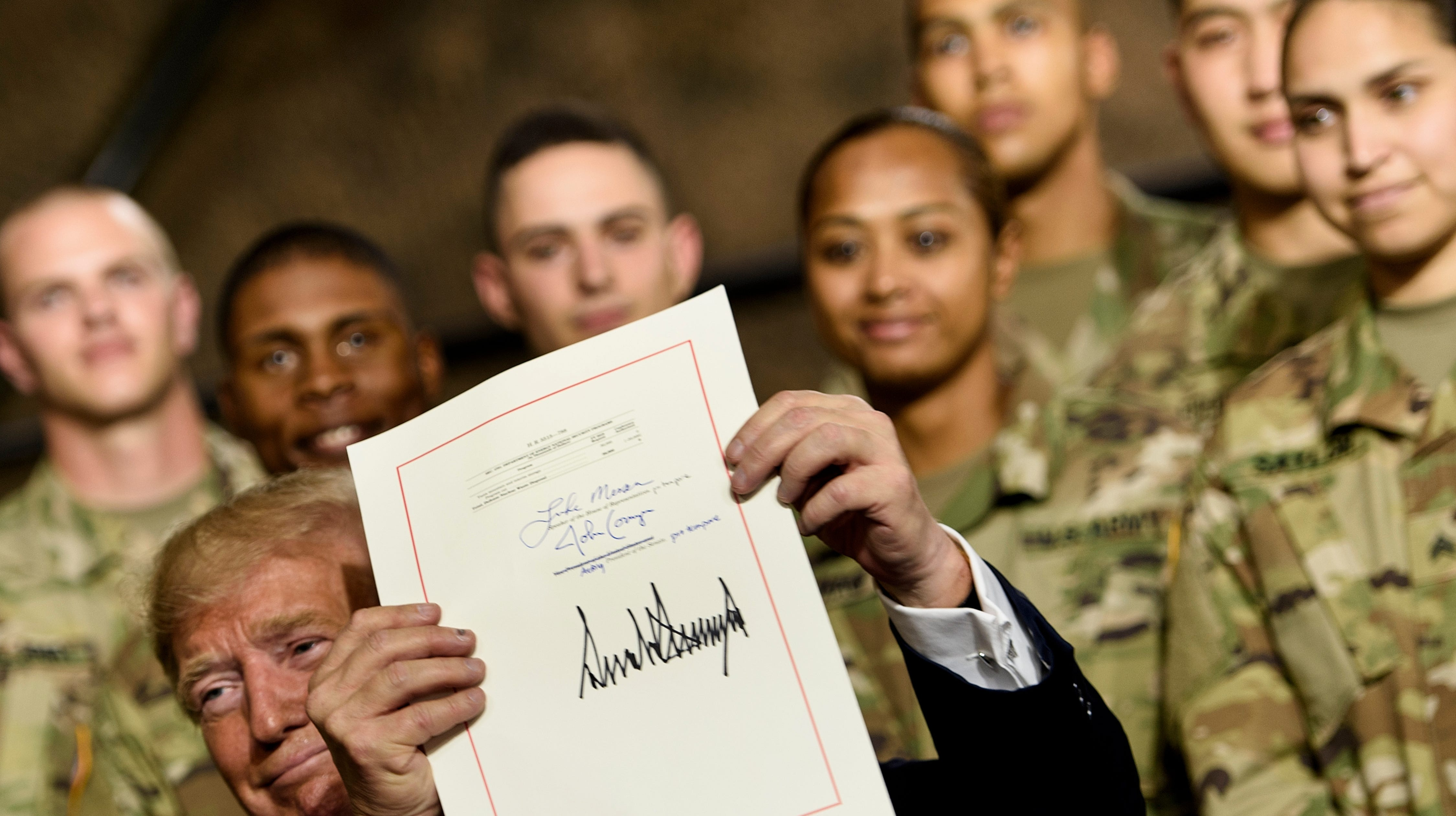 President Donald Trump holds the John S. McCain National Defense Authorization Act for Fiscal Year 2019 after signing it at Fort Drum, New York, on Monday.