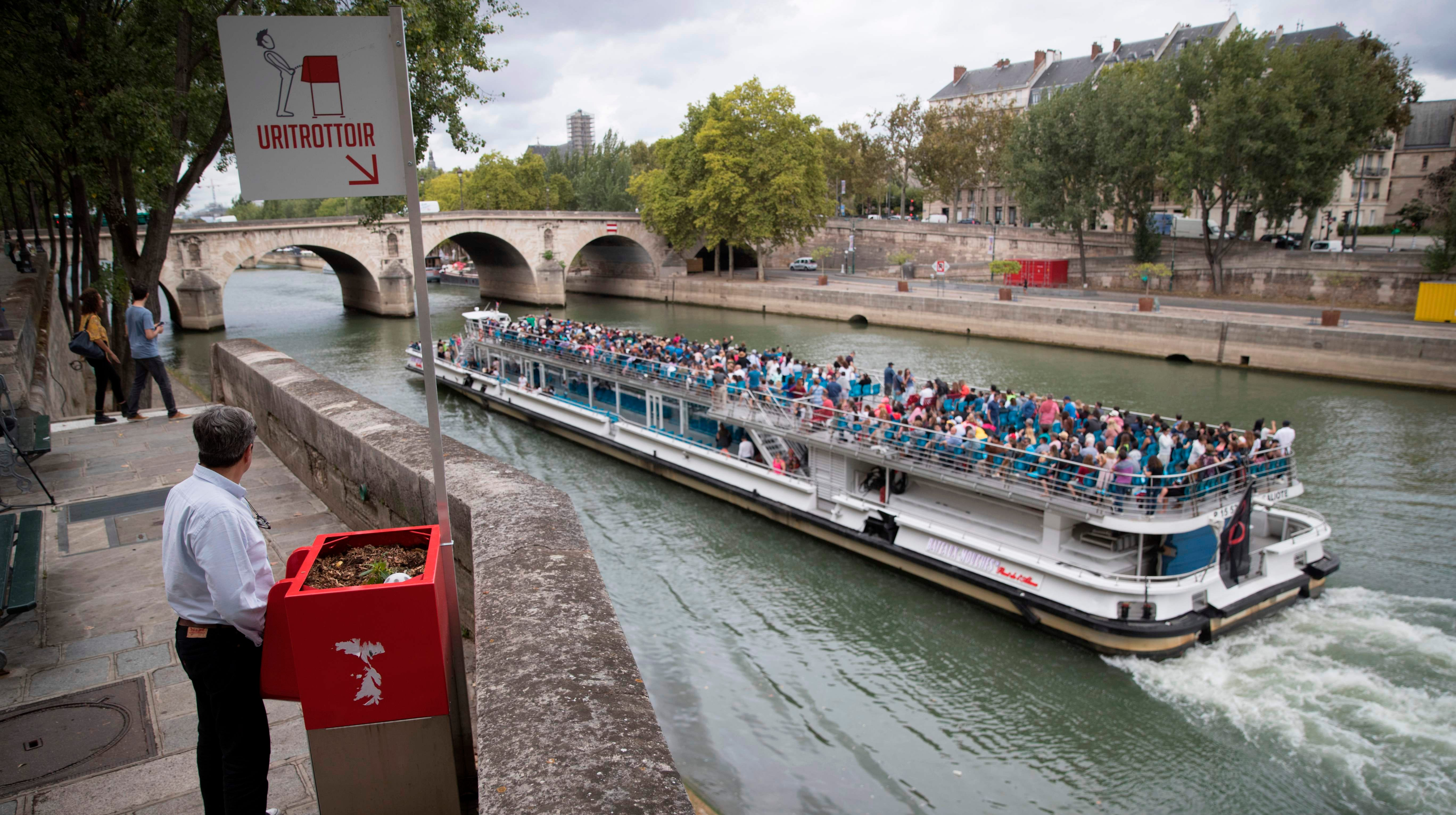 "A man stands at a ""uritrottoir"" public urinal on August 13 on the Saint-Louis island in Paris, as a ""bateau mouche"" tourist barge cruises past."