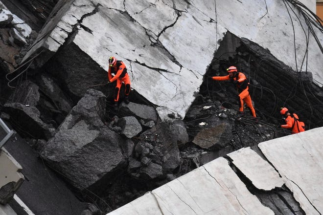 Rescuers at work amid the rubble after a highway bridge collapsed in Genoa, Italy. A large section of the Morandi viaduct upon which the A10 motorway runs collapsed in Genoa on Tuesday. Several people have died, rescue sources said. Several vehicles were crushed under the rubble with dead people inside, the sources said.
