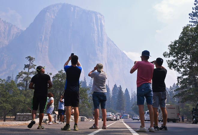 Visitors photograph El Capitan through a thin veil of smoke after Yosemite Valley reopened Tuesday, Aug. 14, 2018 in Yosemite National Park, Calif. The park reopened its scenic valley Tuesday after a nearly three-week closure due to nearby wildfires but advised visitors to expect some smoke in the air and limited lodging and food services in the popular California park. (Eric Paul Zamora/The Fresno Bee via AP) ORG XMIT: CAFRE501