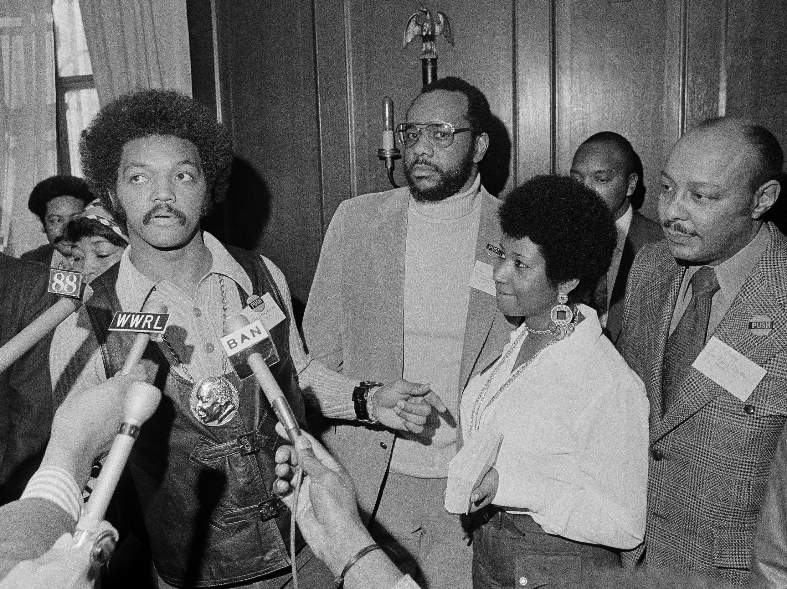 This March 26, 1972 file photo shows the Rev. Jesse Jackson speaking to reporters at the Operation PUSH Soul Picnic in New York as Tom Todd, vice president of PUSH, from second left, Aretha Franklin and Louis Stokes. A person close to Franklin said on Monday that the 76-year-old singer is ill. Franklin canceled planned concerts earlier this year after she was ordered by her doctor to stay off the road and rest up. (AP Photo/Jim Wells, File) ORG XMIT: NYET901