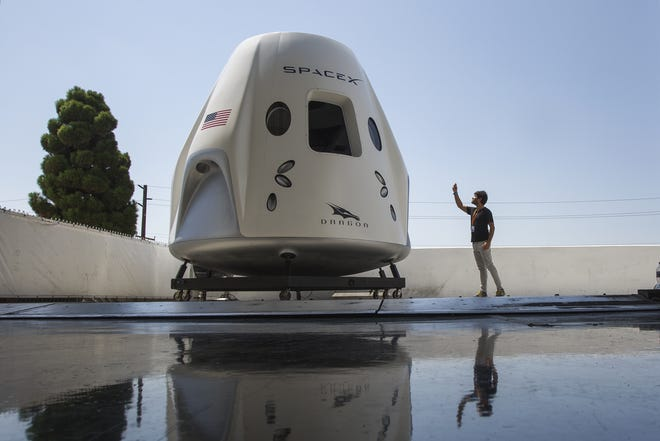 A reporter takes a smart phone photo of a mock up of the Crew Dragon spacecraft during a media tour of SpaceX headquarters and rocket factory on Monday, Aug. 13, 2018, in Hawthorne, California.