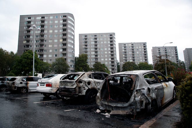 "Burned cars parked at Frolunda Square in Gothenburg, Tuesday,  Aug. 14, 2018. Masked youth torched dozens of cars overnight in Sweden and threw rocks at police, prompting an angry response from the prime minister, who on Tuesday spoke of an ""extremely organized"" night of vandalism."